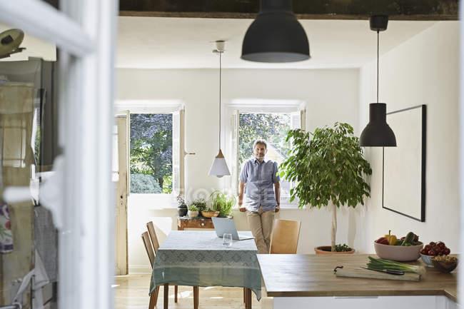 Portrait of mature man standing in dining room — Fotografia de Stock