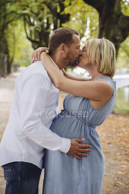 Зрелая беременная пара целуется в парке — стоковое фото