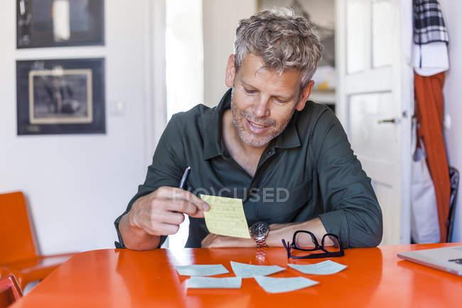 Retrato de conteúdo homem maduro sentado à mesa em casa olhando para o bloco de notas — Fotografia de Stock