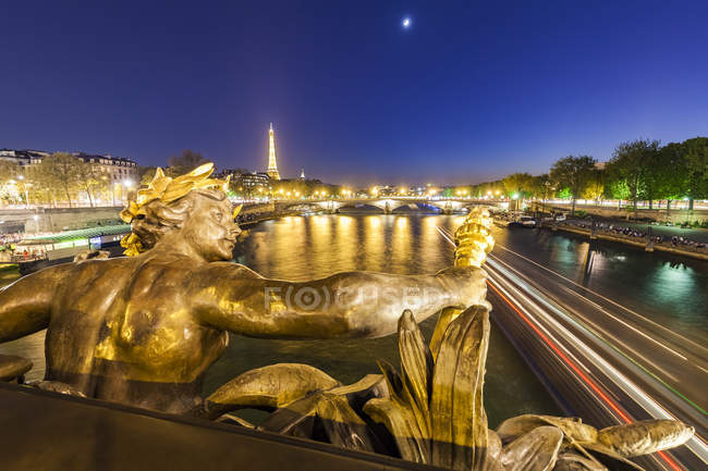 France, Paris, Eiffel Tower, View from Pont Alexandre III bridge, Seine river, bronze sculpture at blue hour — стоковое фото