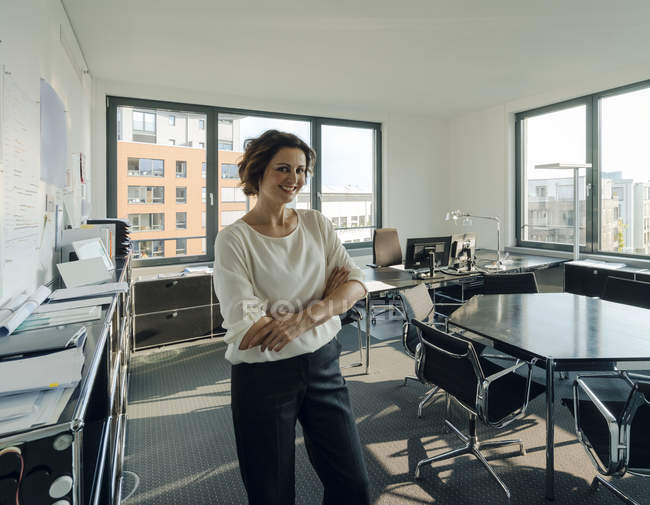 Successful businesswoman standing in her office with arms crossed — Stock Photo