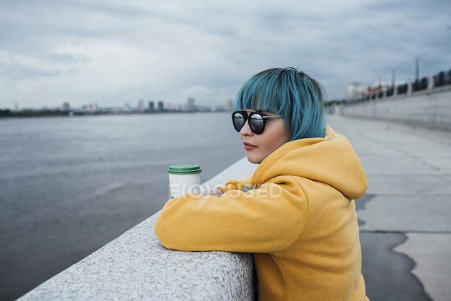 Молодая женщина с окрашенными голубыми волосами опирается на стену и смотрит на расстояние — стоковое фото