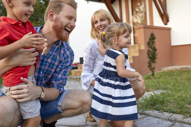 Familia feliz en el jardín de su casa - foto de stock