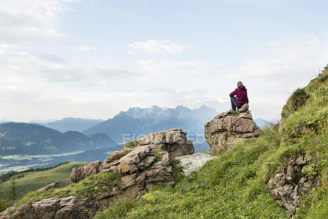 Австрія, Тіроль, Фібербрунн, Вайлдселодер, жінка сидить на камені з видом на гори. — стокове фото