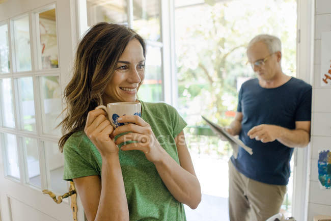 Pareja madura en casa con mujer bebiendo café y hombre leyendo periódico - foto de stock
