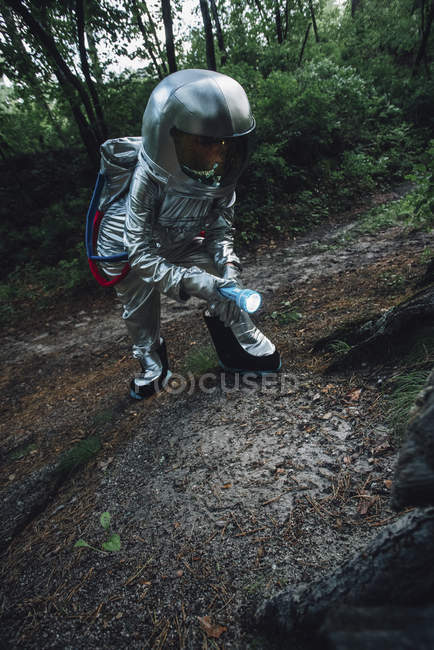 Spaceman exploring nature, using torch in forest — Stock Photo