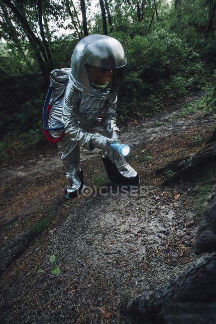 Spaceman explorer la nature, en utilisant la torche dans la forêt — Photo de stock