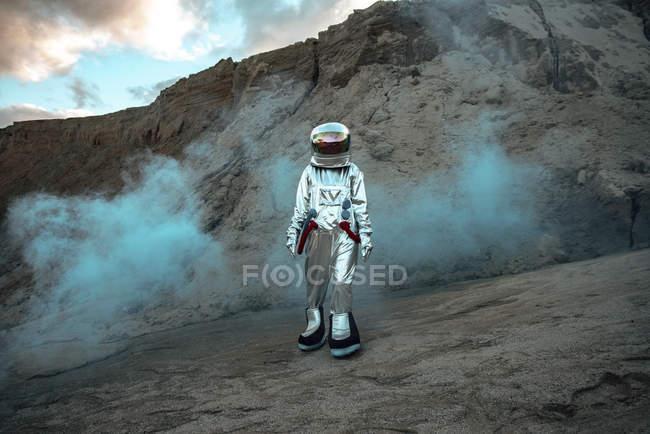 Spaceman explorant une planète sans nom, marchant dans un nuage de poussière — Photo de stock