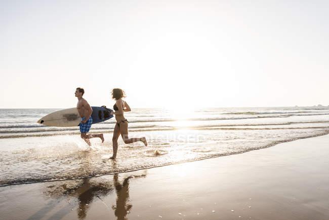 Coppia giovane che corre sulla spiaggia, portando la tavola da surf — Foto stock