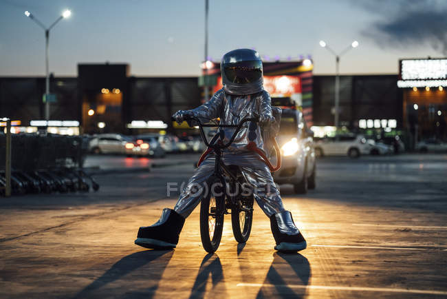 Spaceman in city at night on parking lot with bmx bike — Stock Photo