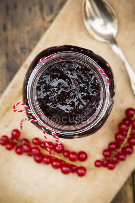 Варенье банку из смородины желе и красной смородины на деревянной доске — стоковое фото