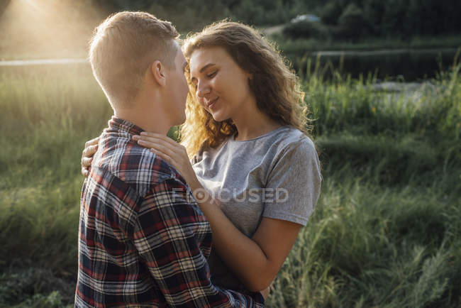 Romantic couple spending time in nature, kissing at sunset — Stock Photo