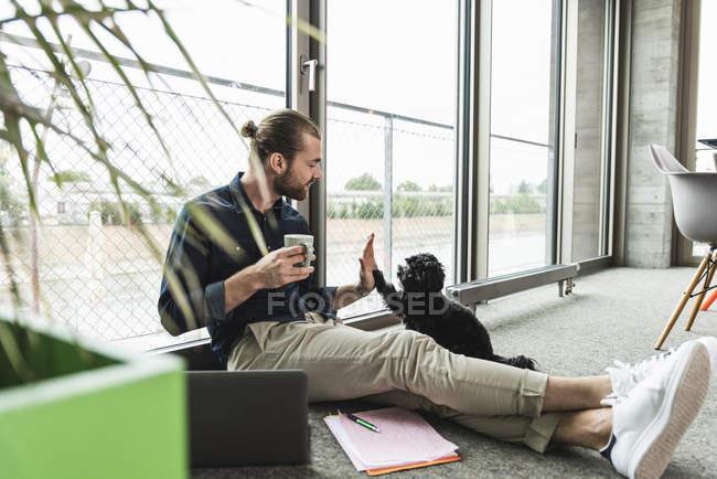 Молодой бизнесмен с ноутбуком сидит на полу в офисе и играет с собакой — стоковое фото