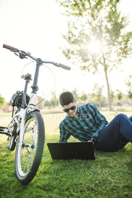 Young man with bicycle using laptop in a park — Stock Photo