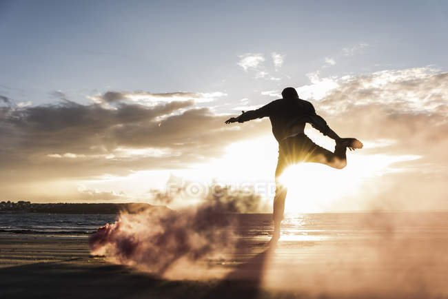 Man doing movement training at beach with colorful smoke at sunset — Stock Photo