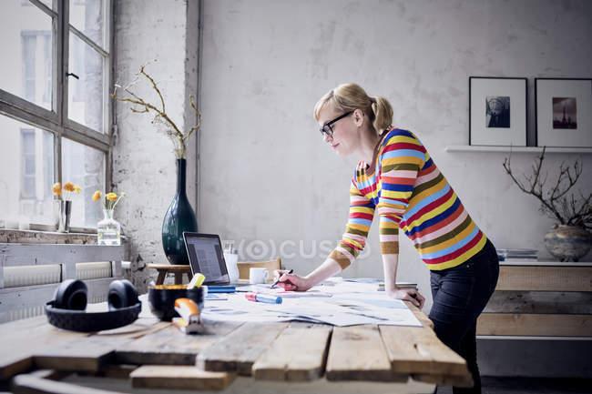 Mujer joven trabajando en el escritorio en el loft - foto de stock