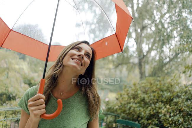Усміхнена зріла жінка, що стоїть в дощ під парасолькою — стокове фото