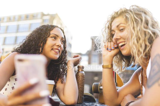 Счастливые подруги обмена сотовый телефон на открытом воздухе — стоковое фото