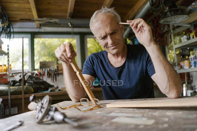 Зрелый человек за рабочим столом в мастерской и думает: — стоковое фото