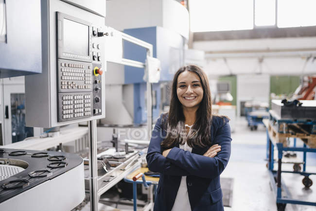 Confident woman working in high-tech enterprise, standing in factory workshop with arms crossed — Stock Photo
