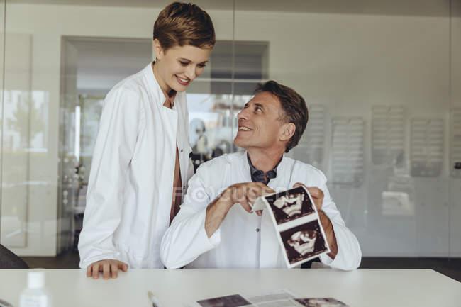 Два врача обсуждают ультразвуковое сканирование плода — стоковое фото