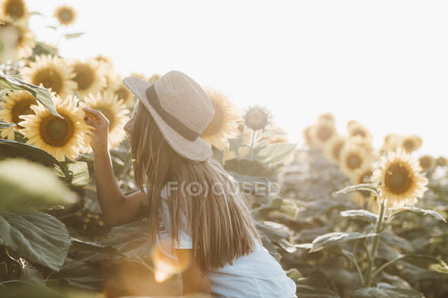 Portrait of young woman standing in field of sunflowers — Stock Photo