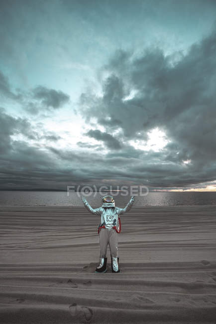 Spaceman standing alone at lake on nameless planet, with raised arms — Stock Photo