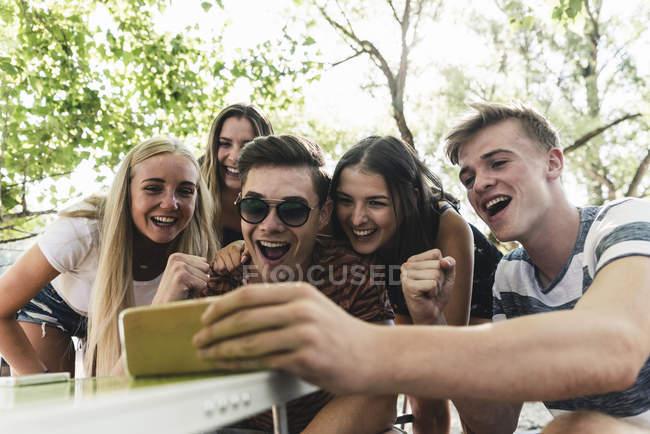 Gruppe glücklicher Freunde schaut im Freien auf ihr Handy — Stockfoto