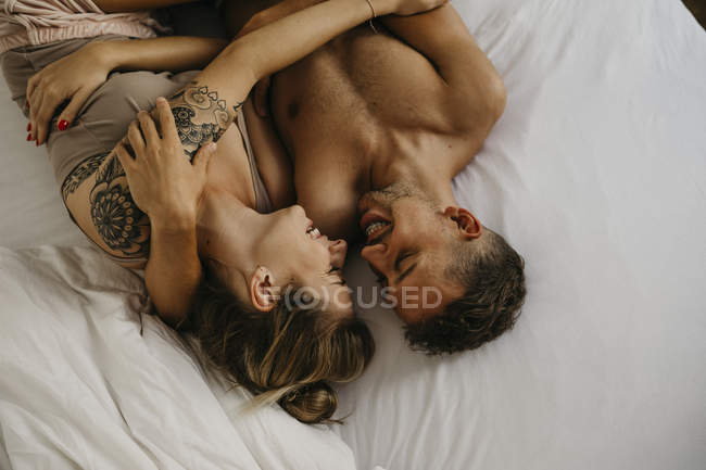 Romantic happy young couple lying in bed — Stock Photo