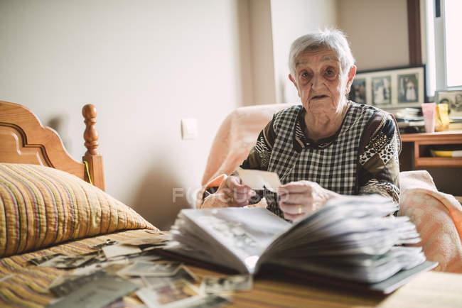Portrait of senior woman adding old photos to a photo album at home — Stock Photo