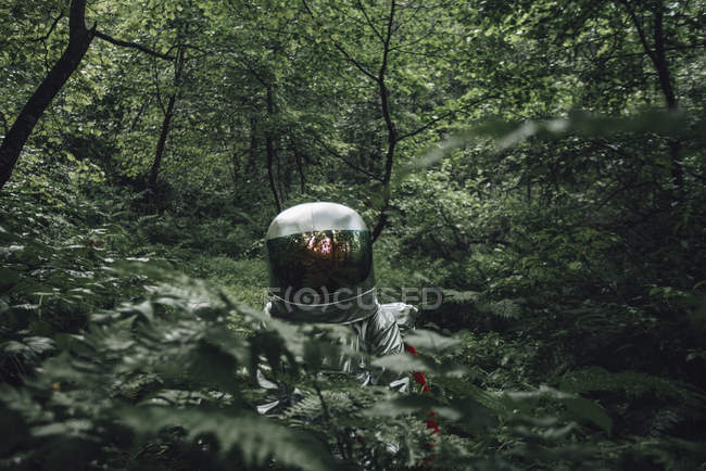 Spaceman exploring nature, standing in green forest — Stock Photo
