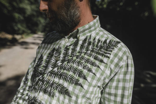 Тень листвы на мужской рубашке — стоковое фото