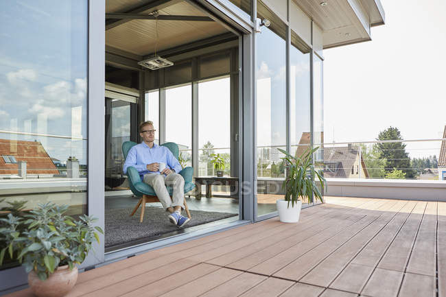 Young man sitting in armchair at balcony door — Stock Photo