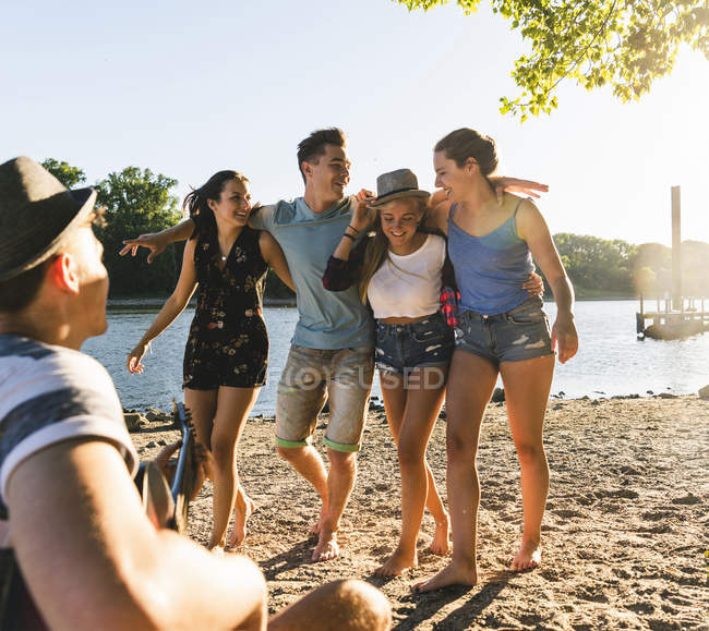 Group of friends having a party at the riverside — Stock Photo