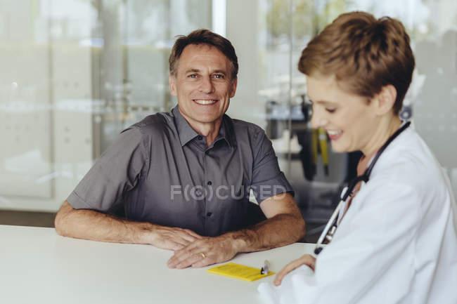 Doctora hablando con la paciente en la práctica - foto de stock
