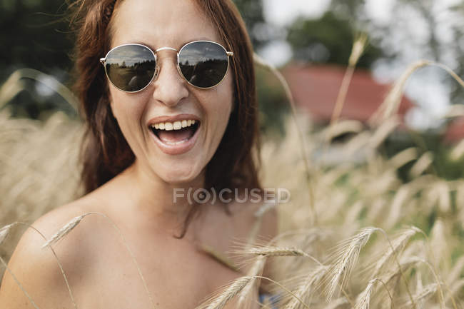 Retrato de mulher feliz usando óculos de sol no campo de trigo — Fotografia de Stock