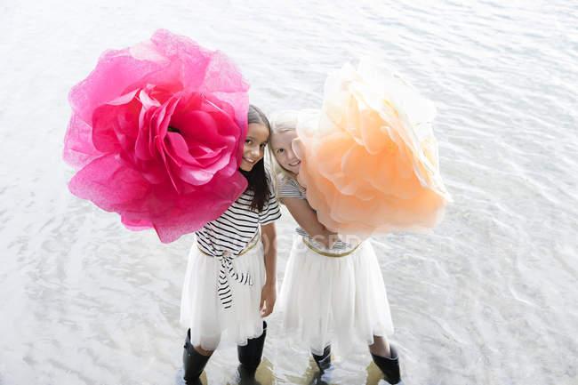 Две девочки стоят в озере с двумя искусственными цветами — стоковое фото