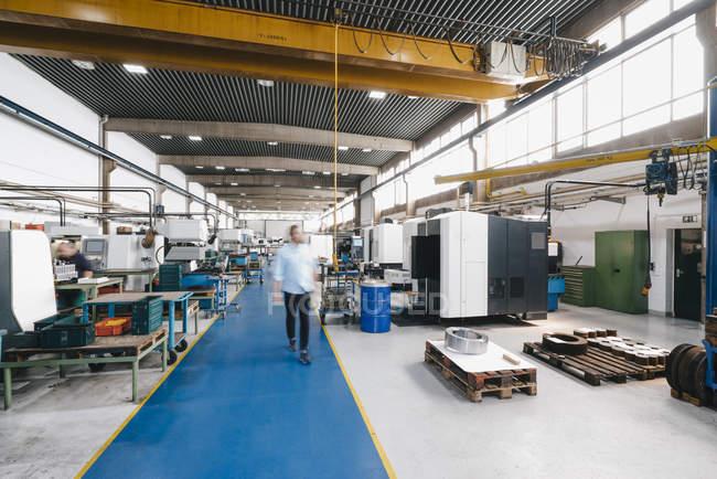 Бизнесмен идет по заводской мастерской — стоковое фото