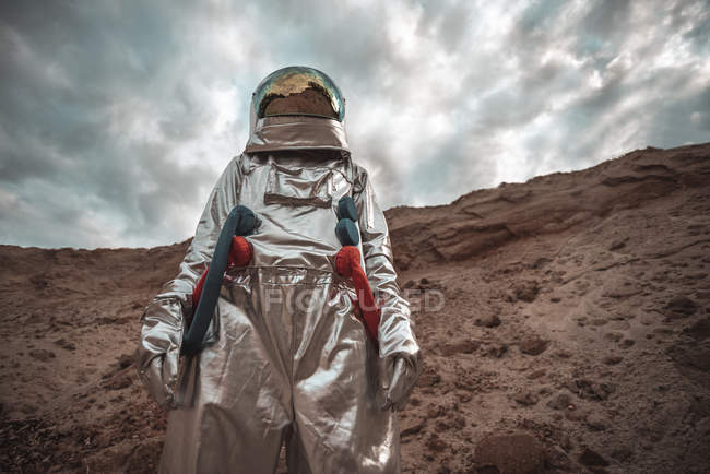Spaceman exploring nameless planet under cloudy sky — Stock Photo