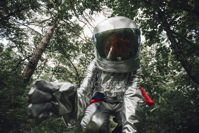 Close-up of spaceman examining plants in forest — Stock Photo