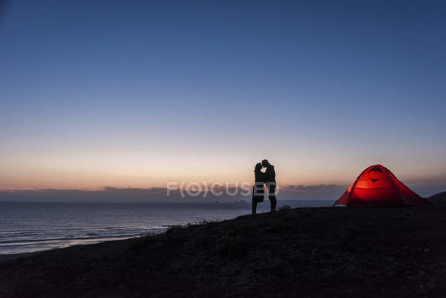 Pareja romántica acampando en la playa, besándose en el crepúsculo - foto de stock