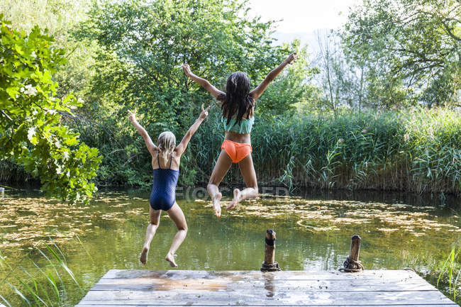 Two carefree girls jumping into pond — Stock Photo
