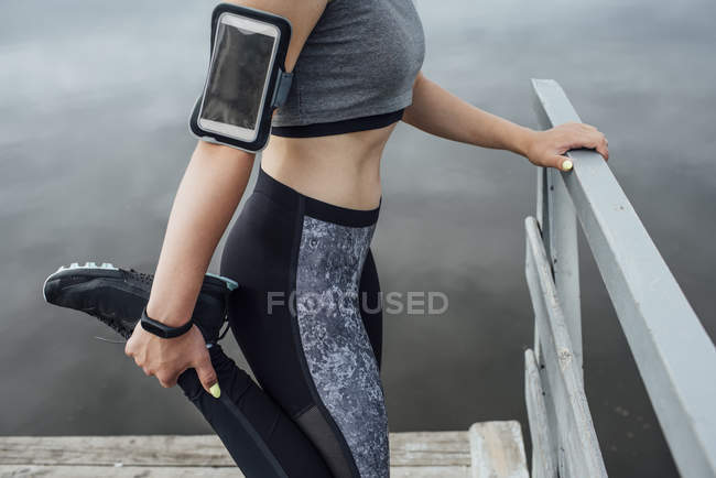 Close-up of athletic woman stretching at riverside — Stock Photo