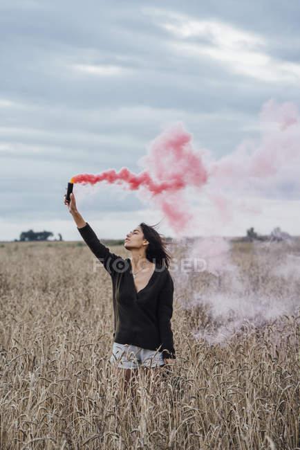 Молодая женщина, стоящая на кукурузном поле с дымовым факелом — стоковое фото