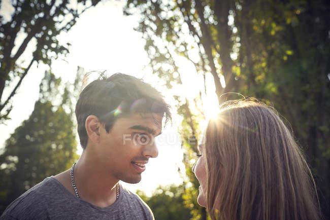 Feliz pareja joven coqueteando en un parque en verano - foto de stock