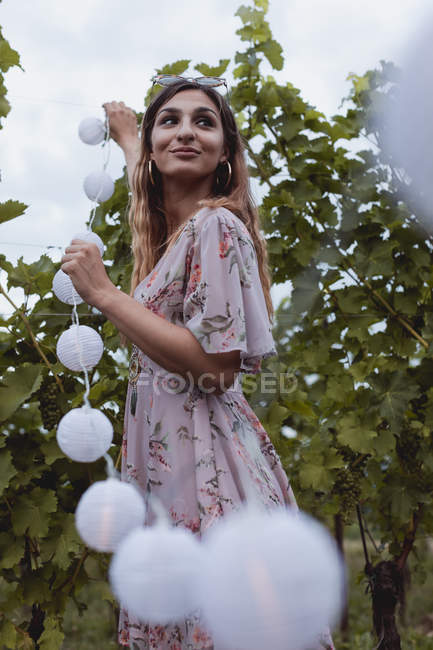 Young woman decorating vineyard with fairy lights for a picnic — Stock Photo