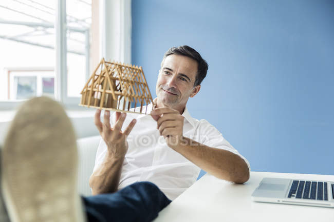 Confident businessman looking at model house in office — Stock Photo