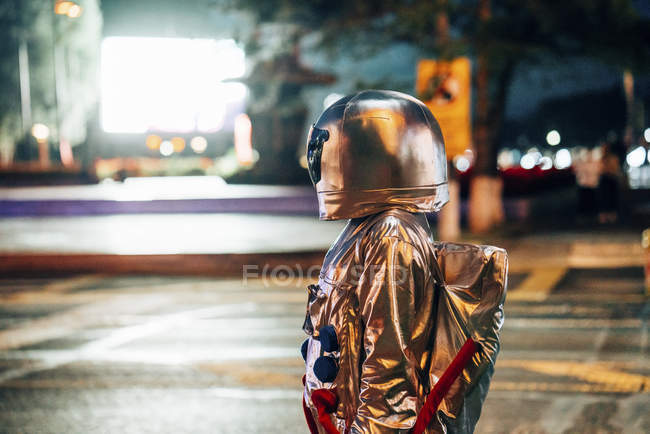 Spaceman standing on square at night attracted by shining projection screen — стоковое фото
