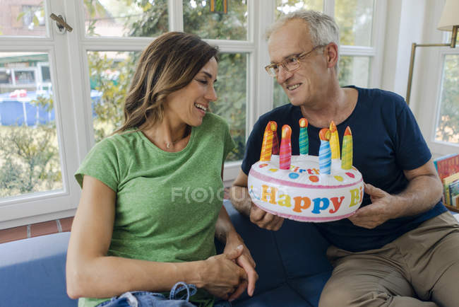 Happy mature couple sitting on couch at home with fake birthday cake — Stock Photo