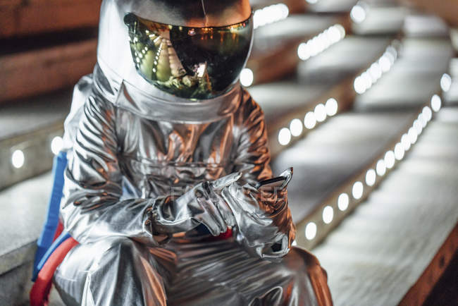 Spaceman sitting on illuminated stairs at night using cell phone — Stock Photo